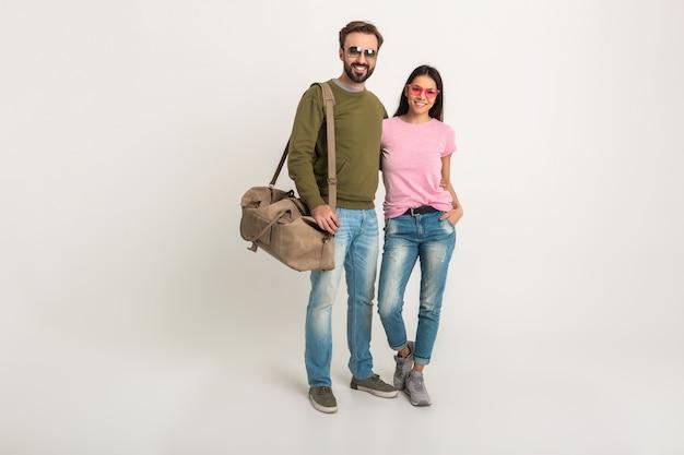 Stilvolles paar isoliert, hübsche lächelnde frau im rosa t-shirt und mann im sweatshirt, das reisetasche hält, gekleidet in jeans, sonnenbrille tragend, spaß zusammen