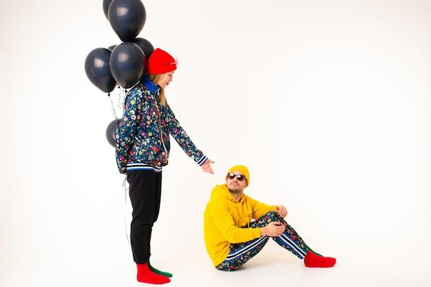Stilvolles paar mann und frau in den bunten kleidern, die mit schwarzen ballons über weißer wand aufwerfen