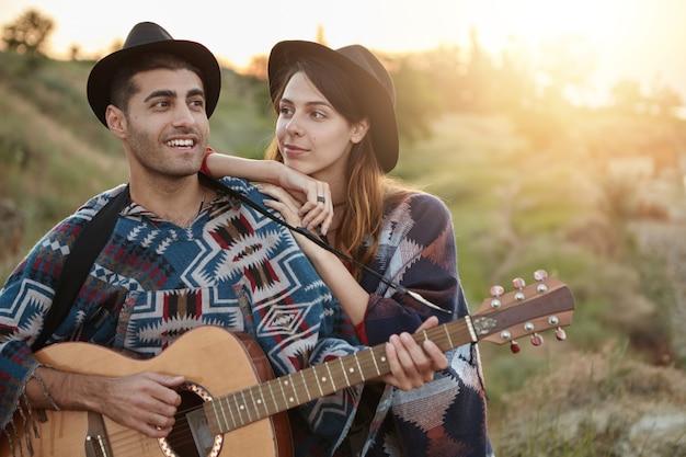 Stilvolles paar mit gitarre auf dem feld