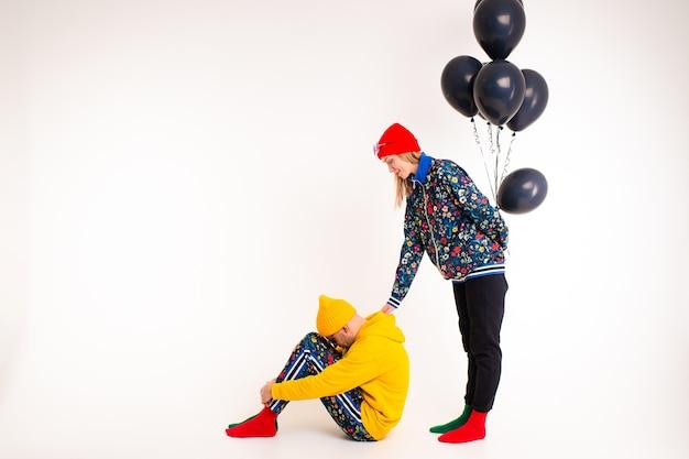 Stilvolles paar von mann und frau in den bunten kleidern, die mit schwarzen ballons aufwerfen