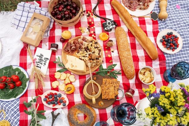 Stilvolles picknick auf dem grünen rasen. frische hörnchen und eine teekanne mit tee auf einer bettdecke nahe einem aus weiden geflochtenen weiblichen hut. instagram-inhalt