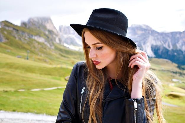 Stilvolles porträt der eleganten frau, die an italienischen dolomitenbergen aufwirft