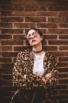 Stilvolles porträt des jungen ernsten modells mit den gekreuzten armen, die modischen leopartd druck-imitatpelzmantel, modesonnenbrille tragen.