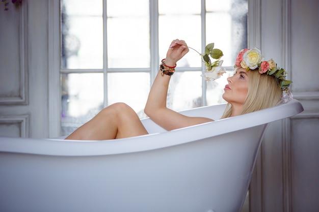 Stilvolles porträt einer jungen schönen frau im badezimmer mit einer blume und einem blumenkranz auf ihrem kopf. das konzept der körperpflege, spa-behandlungen.