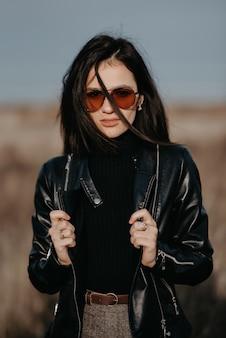 Stilvolles porträt einer modischen frau mit sonnenbrille und lederjacke
