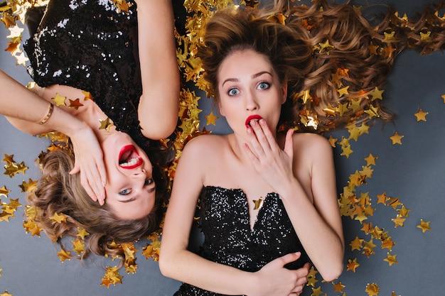 Stilvolles porträt von oben zwei herrliche lustige attraktive junge frauen in schwarzen luxuskleidern, die in goldenen lametta liegen. langes lockiges haar, spaß haben, helle stimmung, geburtstagsfeier.