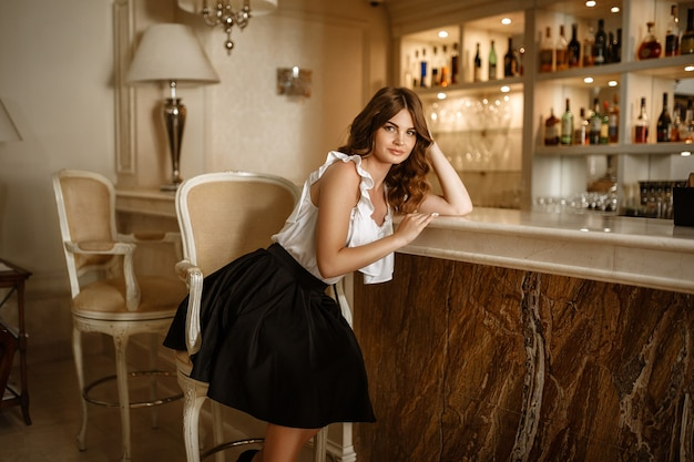 Stilvolles reiches schlankes mädchen im sexy kleid mit gesundem glänzendem haar bei hotelvilla-wohnung