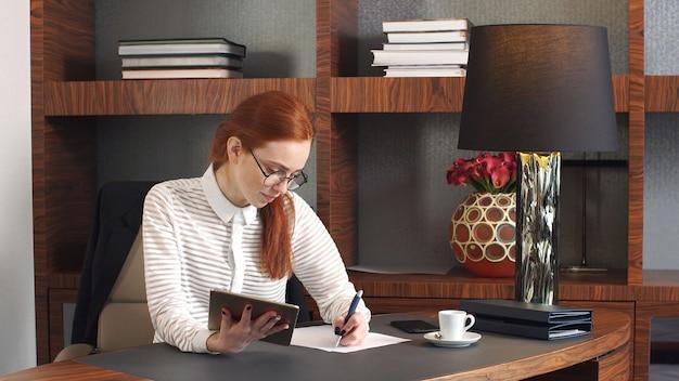 Stilvolles rothaariges mädchen, das zu hause büro arbeitet