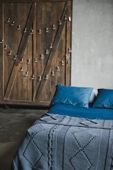 Stilvolles schlafzimmer in der dachbodenart mit grauen farben. bett mit einem dunkelblauen bett.