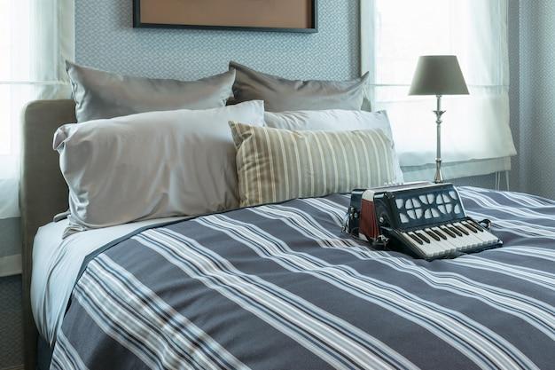 Stilvolles schlafzimmer-interieur mit gestreiften kissen und dekorativem akkordeon auf dem bett