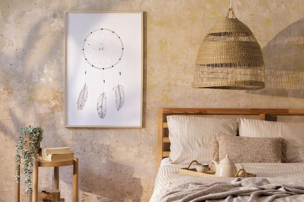 Stilvolles schlafzimmer-interieur mit posterrahmen, designmöbeln, pflanzen, rattan-dekoration und eleganten persönlichen accessoires. schöne beige bettwäsche, decke und kissen.