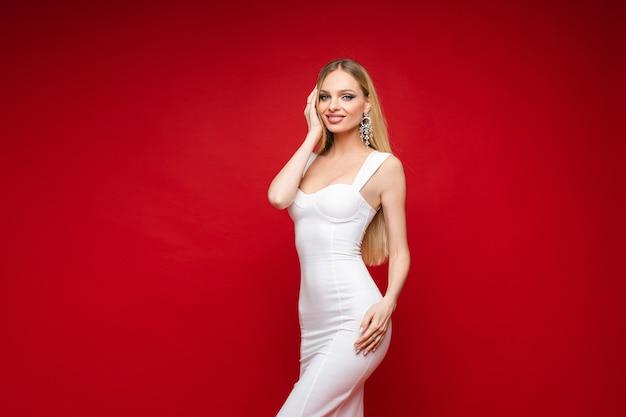 Stilvolles schlankes mädchenmodell im weißen festlichen kleid, das auf rotem studio lächelt und aufwirft