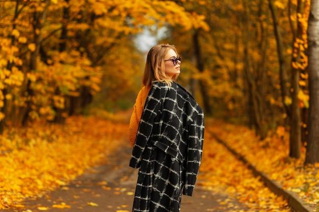 Stilvolles schönes junges frauenmodell in trendiger sonnenbrille in einem modischen sommerhut mit oberteil und hose zieht schuhe in der stadt an