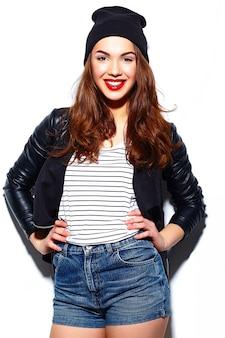 Stilvolles schönes junges glückliches lächelndes frauenmodell des zaubers mit den roten lippen im zufälligen stoff in der schwarzen mütze