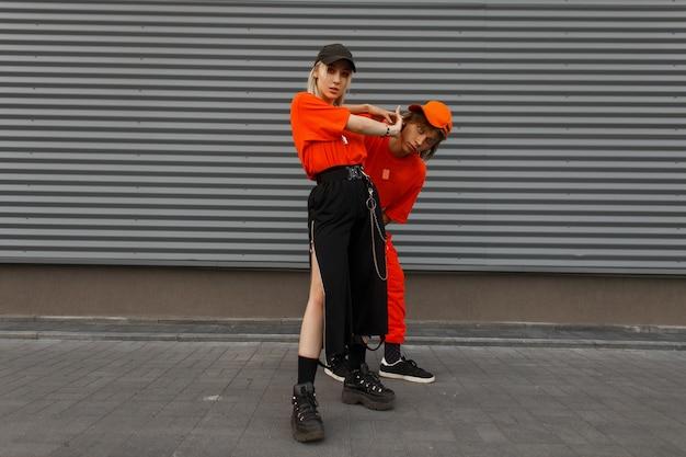 Stilvolles schönes junges paar in modischer orange kleidung mit kappen nahe der grauen metallwand