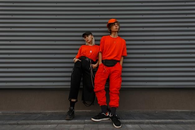 Stilvolles schönes junges paar in trendigen orangefarbenen kleidern mit kappen nahe der grauen metallwand