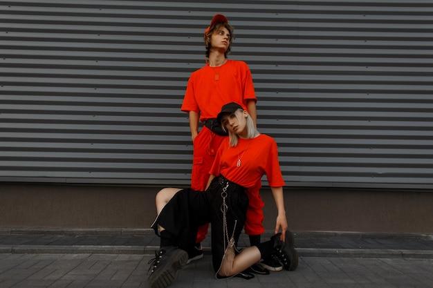 Stilvolles schönes junges paar mit mützen in modischen orangefarbenen kleidern mit turnschuhen, die nahe der grauen metallwand aufwerfen