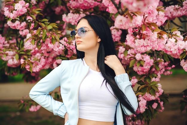 Stilvolles schönes mädchen in gläsern. frühlingstag. schöne kirschblüten-sakura im frühling. frühlingsrosa sakura-blüte. modisches mädchen in der trendigen brille.