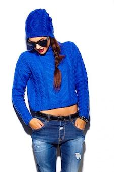 Stilvolles schönes modell der jungen frau des zaubers mit den roten lippen im blauen strickjackenhippie-stoff im beanie