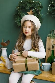 Stilvolles schönes molliges mädchen, das geschenke auf ihrem schoss hält und in der küche, verziert für weihnachten und neues jahr sitzt
