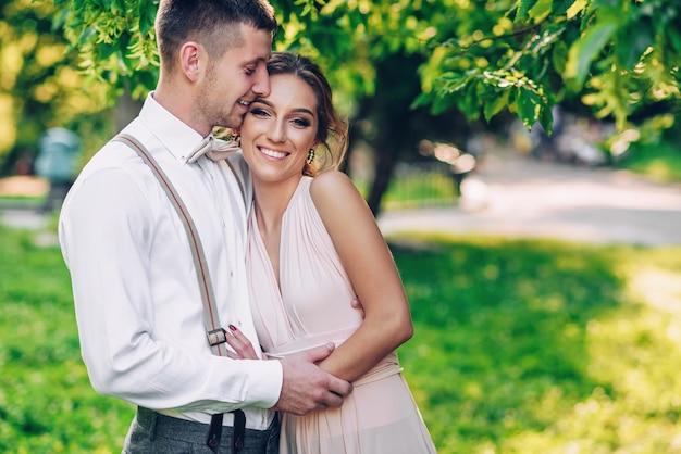 Stilvolles schönes paar in warmen umarmungen unter dem baum im park bei sonnenuntergang