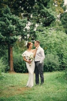 Stilvolles schönes paar in warmen umarmungen unter dem baum im park