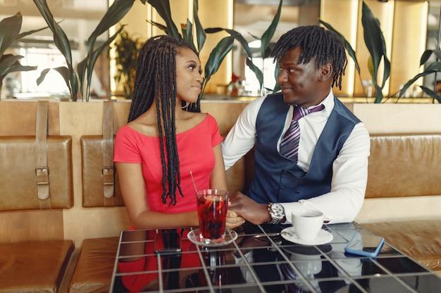 Stilvolles schwarzes paar, das in einem café sitzt und einen kaffee trinkt