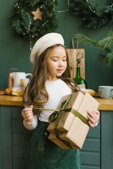 Stilvolles sechsjähriges mädchen in einem barett hält ein weihnachtsgeschenk und öffnet es