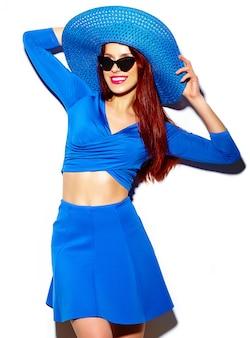 Stilvolles sexy lächelndes lustiges schönes modell der jungen frau des blickes der hohen mode im hellen blauen zufälligen hippie-stoff des sommers im sonnenhut