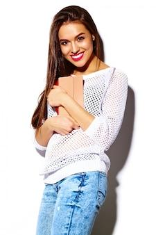 Stilvolles sexy lächelndes schönes modell der jungen frau des blickes der hohen mode zauber im hellen weißen zufälligen hippie-stoff des sommers mit buntem kupplungsgeldbeutel