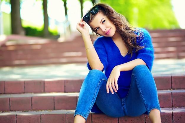 Stilvolles sexy lächelndes schönes sinnliches modell der jungen frau des blickes der hohen mode im hellen hippie-stoff des sommers in den blue jeans, die in der straße sitzen