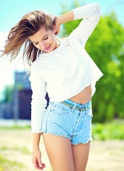 Stilvolles sexy lächelndes schönes sinnliches modell der jungen frau des blickes der hohen mode im hellen hippie-stoff des sommers in der kurzen jeanshose in der straße