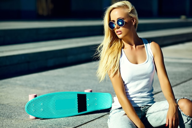 Stilvolles sexy schönes junges blondes vorbildliches mädchen des blickes der hohen mode zauber im hellen zufälligen hippie des sommers kleidet mit dem skateboard, das in der straße sitzt