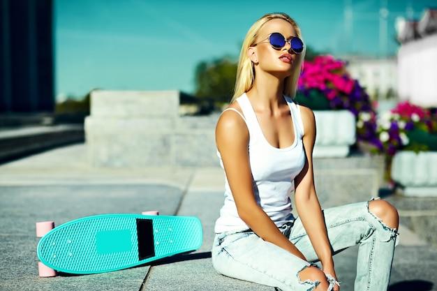 Stilvolles sexy schönes junges blondes vorbildliches mädchen des blickes der hohen mode zauber im hellen zufälligen hippie des sommers kleidet mit skateboard hinter blauem himmel in der straße