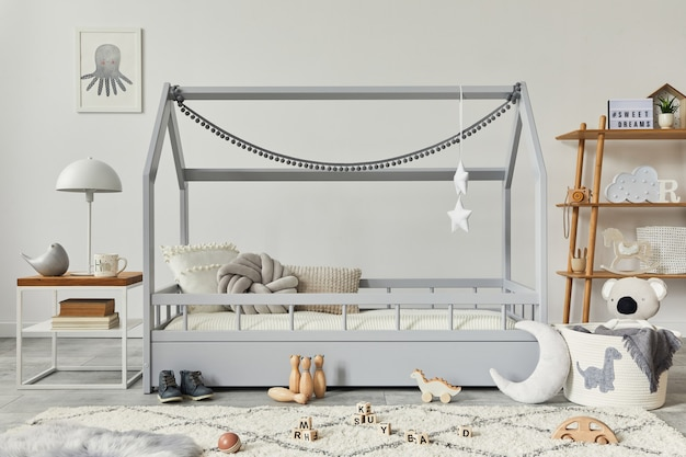 Stilvolles skandinavisches kinderzimmer mit kreativem holzbett, holzwürfel, lampe, holzregal, plüsch- und holzspielzeug und hängenden textildekorationen. graue wände. vorlage.