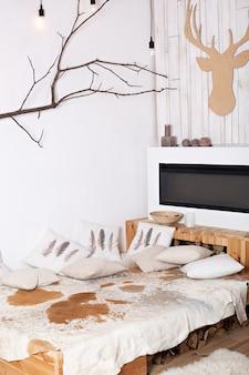 Stilvolles skandinavisches minimalistisches weihnachtsinterieur mit elegantem sofa. komfort nach hause. modernes landhaus interieur mit holzbett, brennholz, kamin. weihnachtsdekoration in einem raum idoor.
