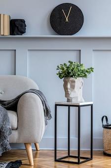 Stilvolles skandinavisches wohnzimmer mit grauem sofa, plaid, schwarzer uhr, holzverkleidung mit regal, marmorhocker, pflanzen und eleganten persönlichen accessoires in design-wohnkultur.
