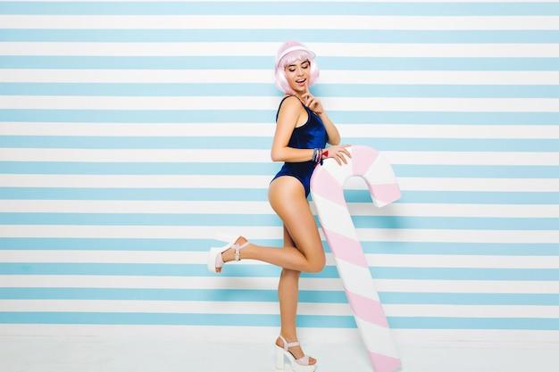 Stilvolles sommermodell im blauen badeanzug mit geschnittener rosa frisur, die spaß mit großem lutscher auf gestreifter blauweißer wand hat. junge sexy frau, erstaunlich, lächelnd, strandparty, genießen.