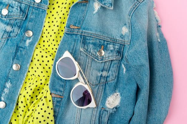 Stilvolles sommeroutfit für frau auf pastellrosa hintergrund