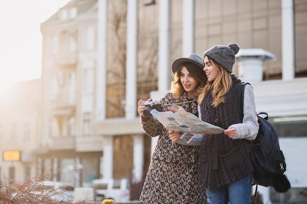 Stilvolles stadtporträt von zwei modischen frauen, die im modernen stadtzentrum europas gehen. modische freunde, die mit rucksack, karte, kamera reisen, foto machen, touristen, einen verlorenen platz für text bekommen.