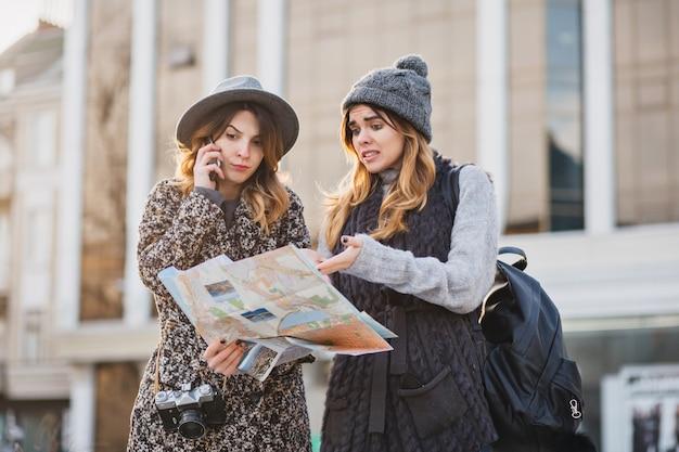 Stilvolles stadtporträt von zwei modischen frauen, die im modernen stadtzentrum europas gehen. modische freunde, die mit rucksack, karte, tourist reisen, verlieren sich und telefonieren.