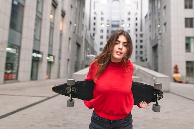 Stilvolles straßenmädchen in freizeitkleidung steht mit einem longboard in den händen des hintergrunds der modernen architektur. mädchen-skater wirft zur kamera auf dem hintergrund eines modernen gebäudes auf.