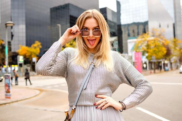 Stilvolles straßenporträt der blonden frau, die das glamouröse graue outfit an hand zu ihrer sonnenbrille trägt