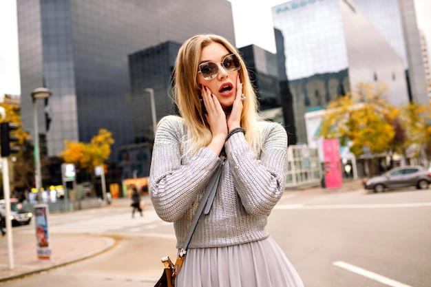 Stilvolles straßenporträt der blonden frau, die glamouröses graues outfit an der hand zu ihrer sonnenbrille, geschäftszentrumbereich trägt. überraschtes gesicht.