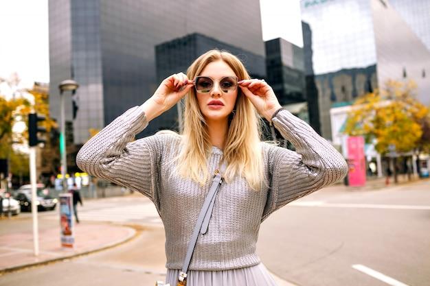 Stilvolles straßenporträt der blonden frau, die glamouröses graues outfit an der hand zu ihrer sonnenbrille, geschäftszentrumbereich trägt.