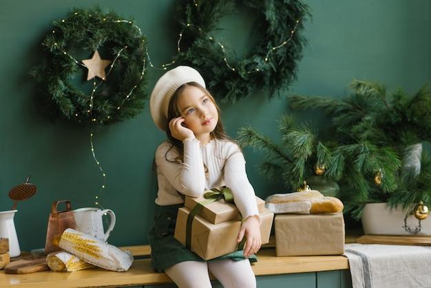 Stilvolles süßes mädchen, das auf ihrem schoß weihnachts- oder neujahrsgeschenk im inneren der smaragdgrünen küche und träume hält