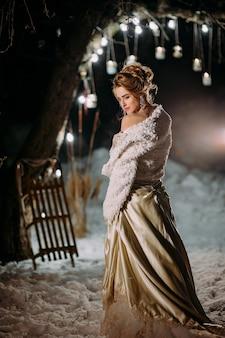 Stilvolles tausendjähriges mädchen ein winterabend mit lichtern