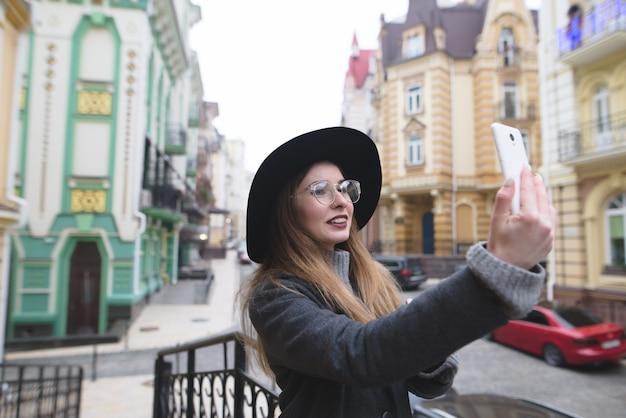 Stilvolles touristenmädchen nimmt selfie