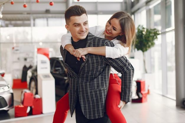 Stilvolles und elegantes paar in einem autosalon