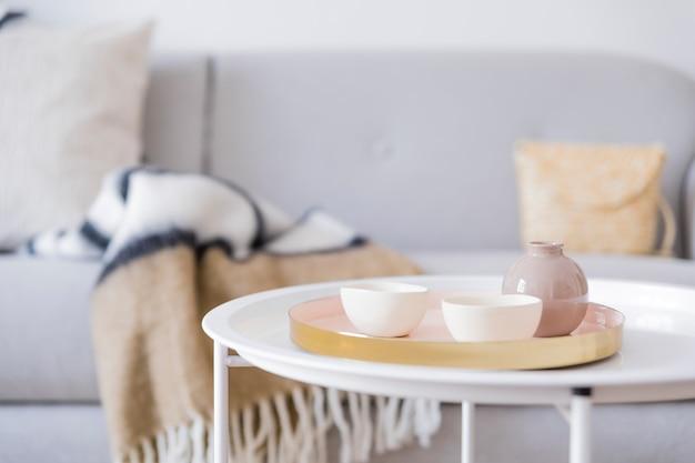 Stilvolles und gemütliches interieur des wohnzimmers mit eleganten rattan-accessoires, design-sessel, grauem sofa, möbeln, airplants und holzregal. neutrale wohnkultur.